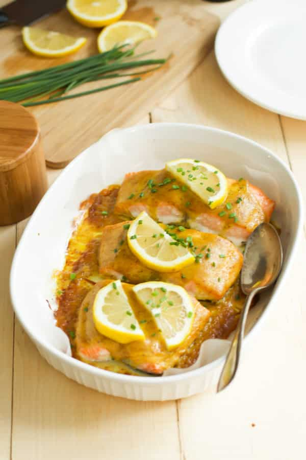 Maple mustard salmon in a baking dish with a spoon inside.