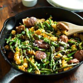 Sausage asparagus quinoa pasta in a cast iron skillet.