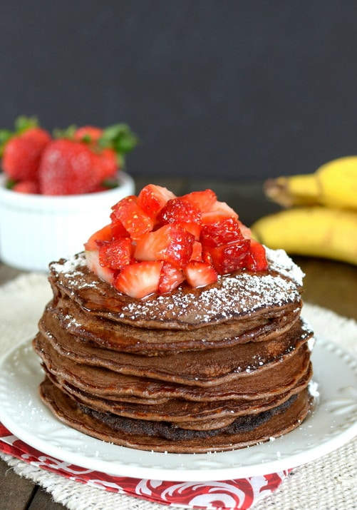 A stack of skinny chocolate banana oatmeal pancakes with strawberries on top.