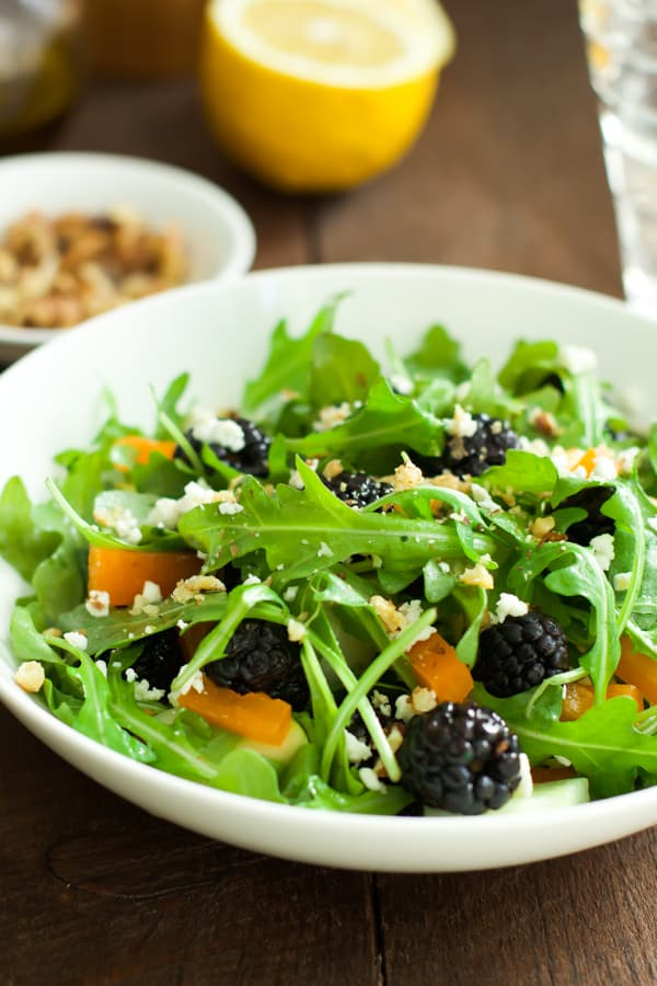 A white bowl containing an arugula blackberry salad