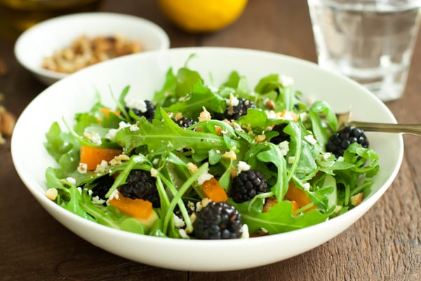 A close up of arugula blackberry salad.