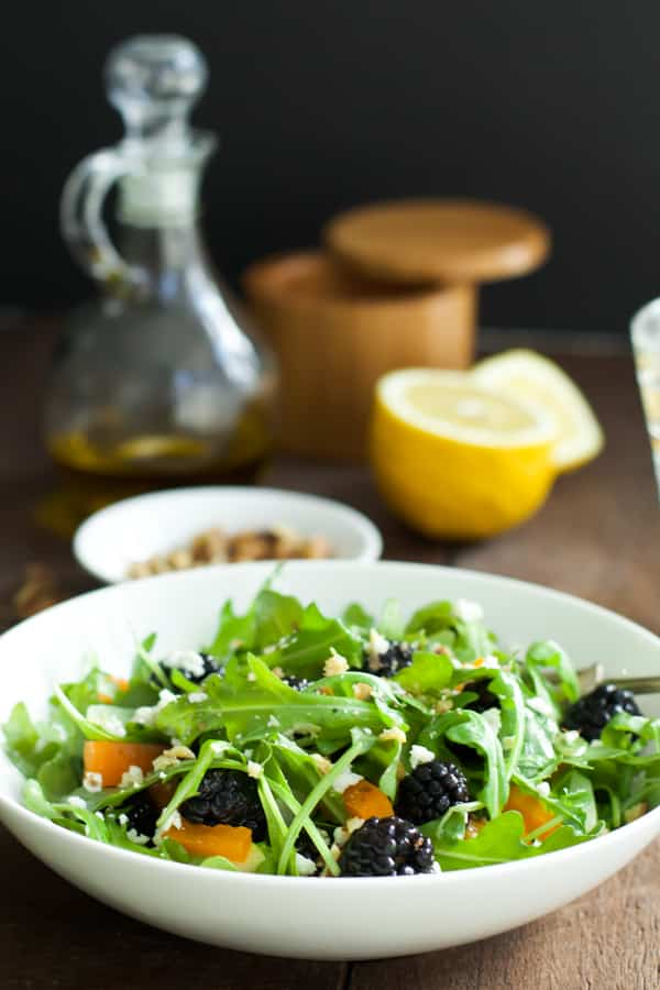 An arugula blackberry salad with oil, lemon, and salt in the background.