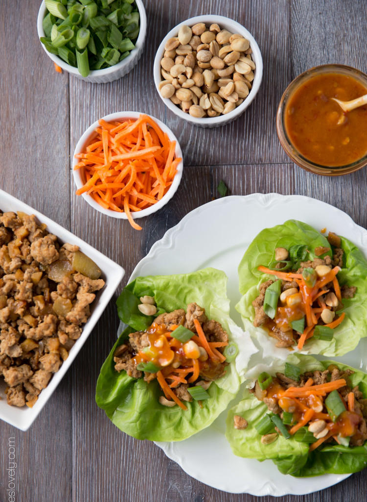 Three Asian turkey lettuce wrap on a plate with carrots, peanuts, green onions, sauce, and the filling in bowls beside it.