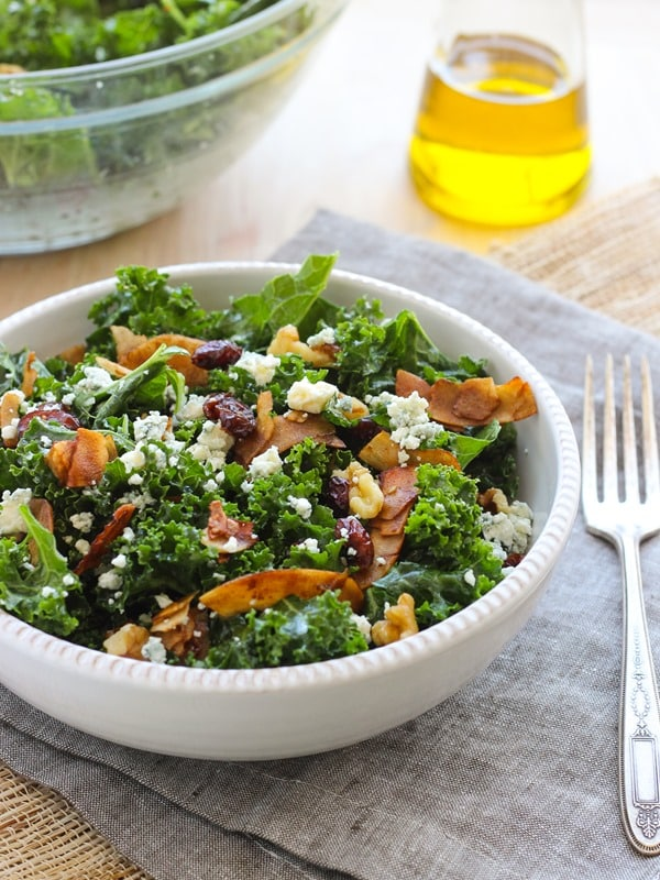 Kale salad with vegan coconut bacon in a white bowl.