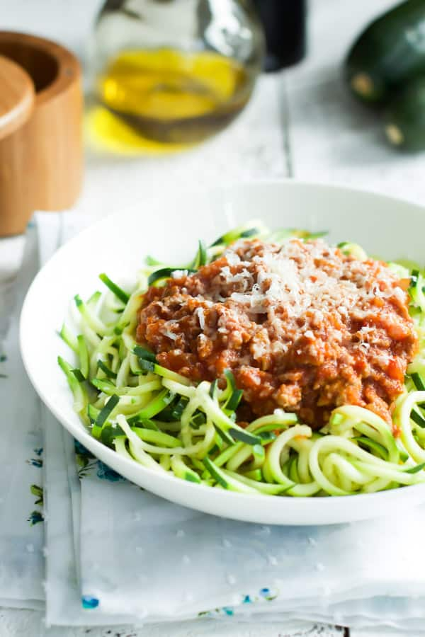 A white bowl containing turkey bolognese with zucchini pasta.