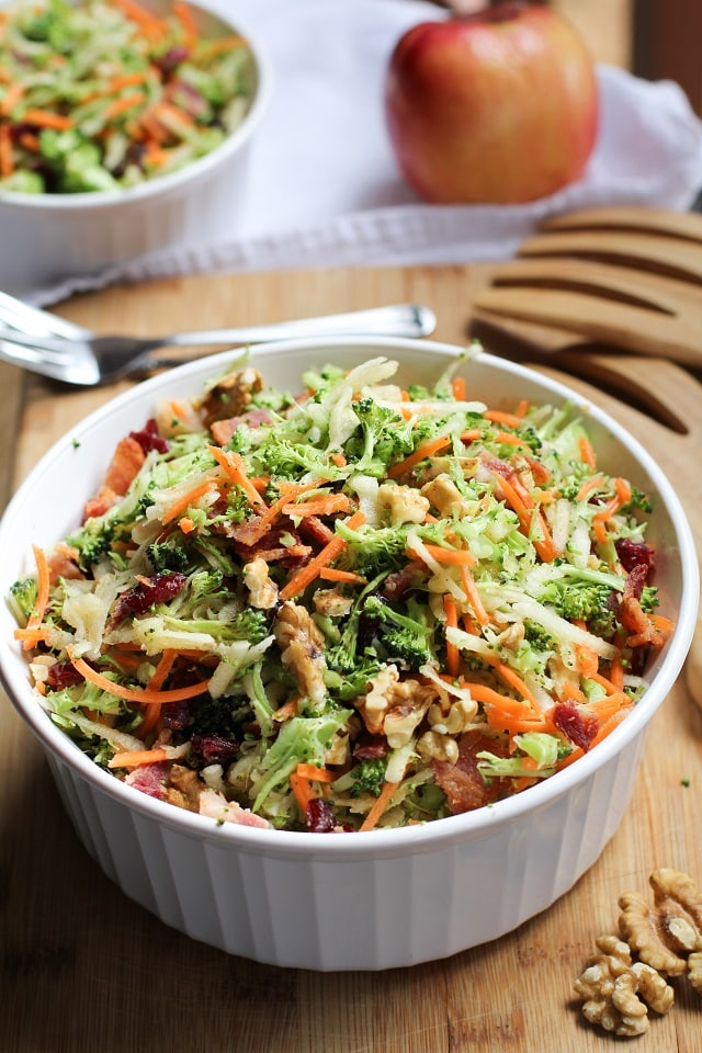 Grated broccoli salad with carrots, apples, and dried cranberries in a bowl.