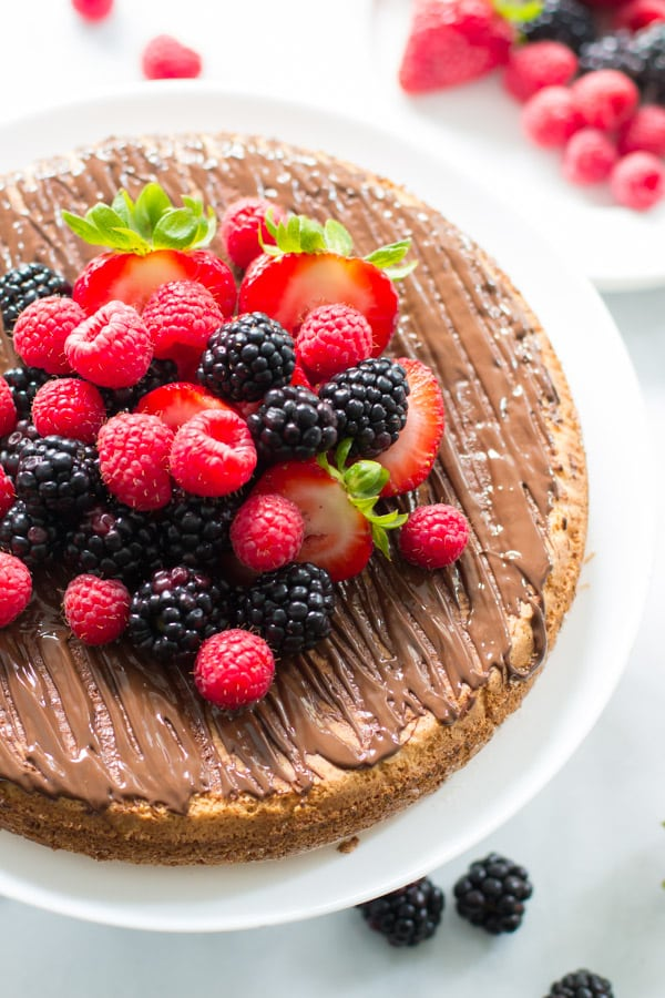 An overhead image of an almond cake with berries on a cake stand.