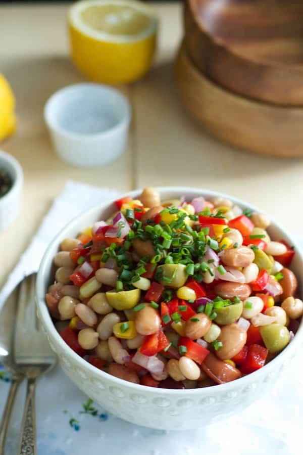 A white bowl of bean medley salad.