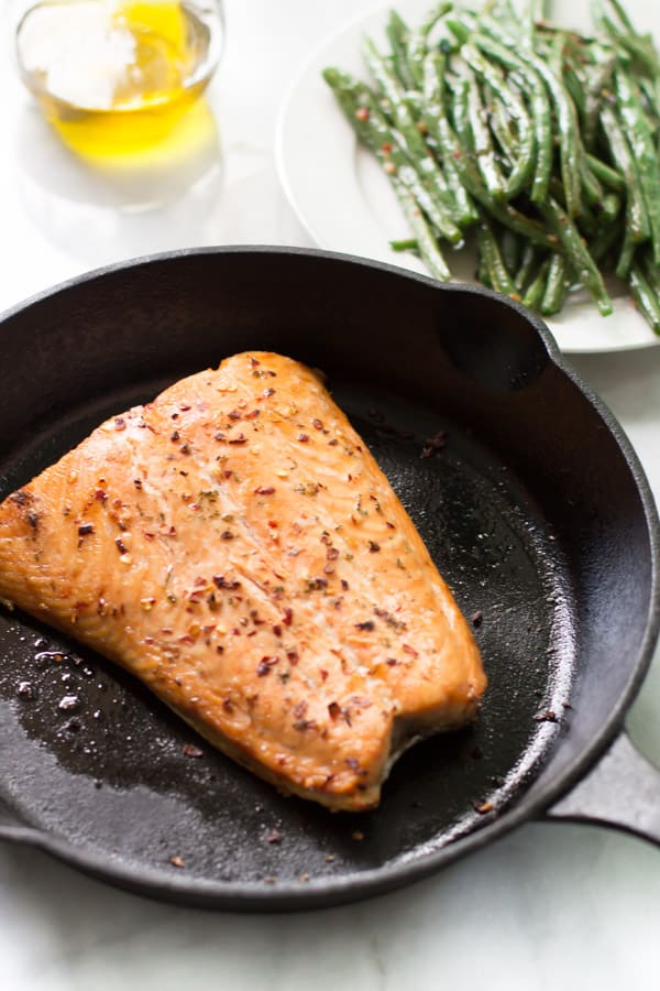 A skillet containing a broiled salmon.
