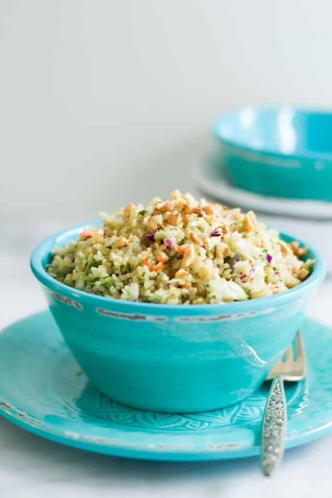 A blue bowl of quinoa cabbage salad.