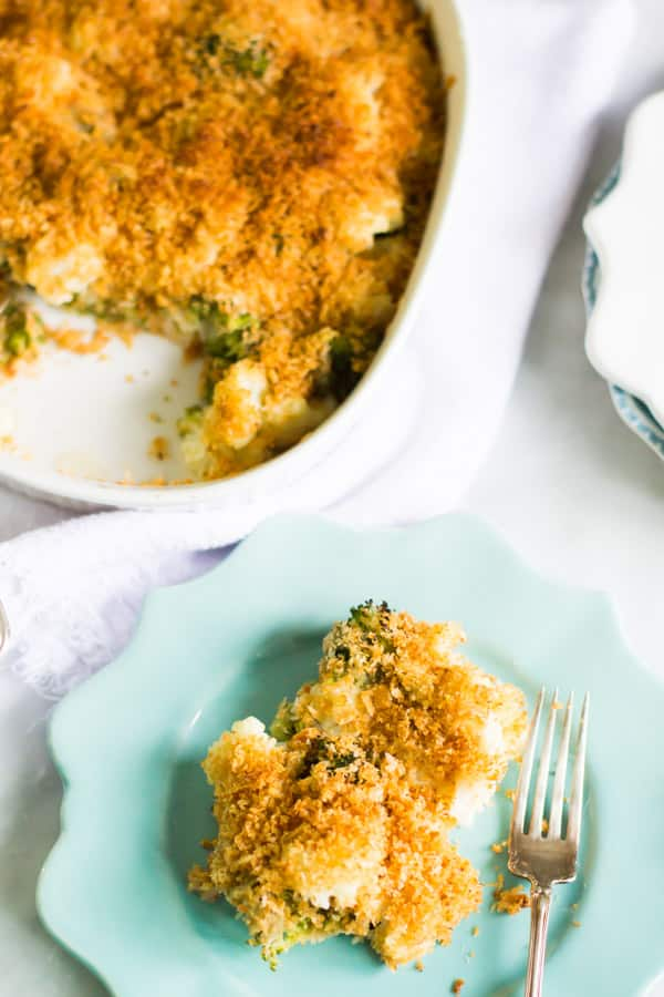 A plate of cheesy broccoli cauliflower bake beside the casserole dish.
