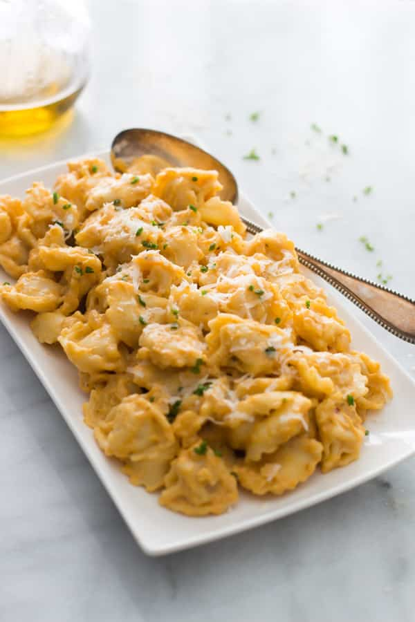A plate of tortellini with pumpkin sauce.