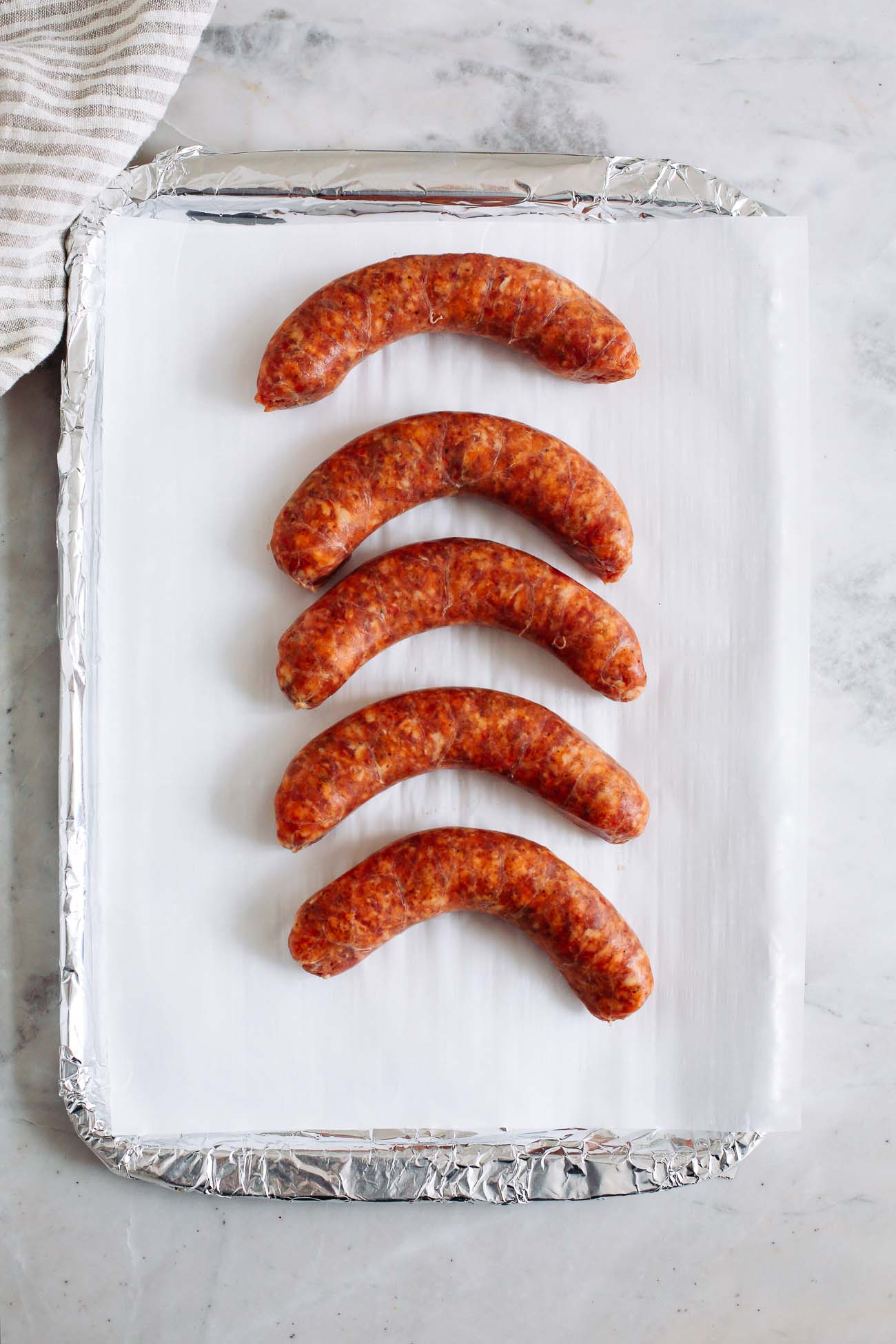A lined sheet pan with sausage on it.