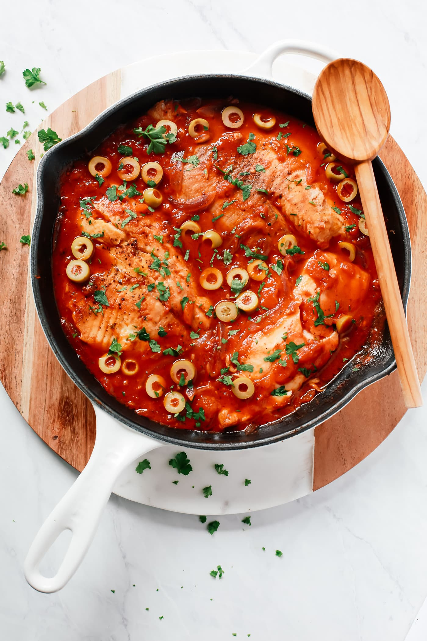 overhead view of a white skillet containing tilapia in a tomato sauce