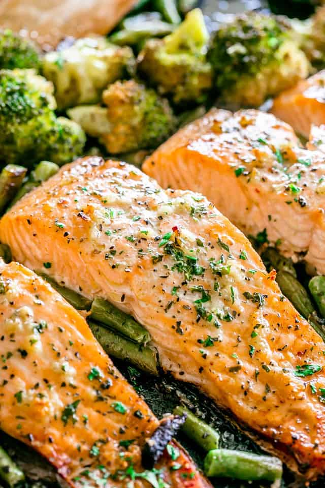 3 pieces of fish in a baking sheet with gree beans and broccoli