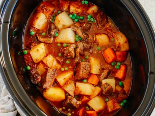 Healthy slow cooker beef stew inside of a black slow cooker bowl.