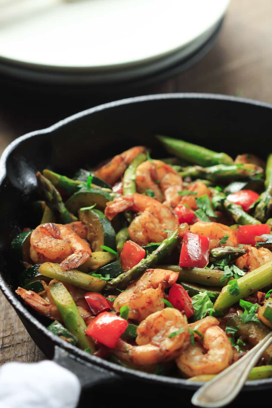 close up view of a cast iron skillet containing shrimp and vegetables