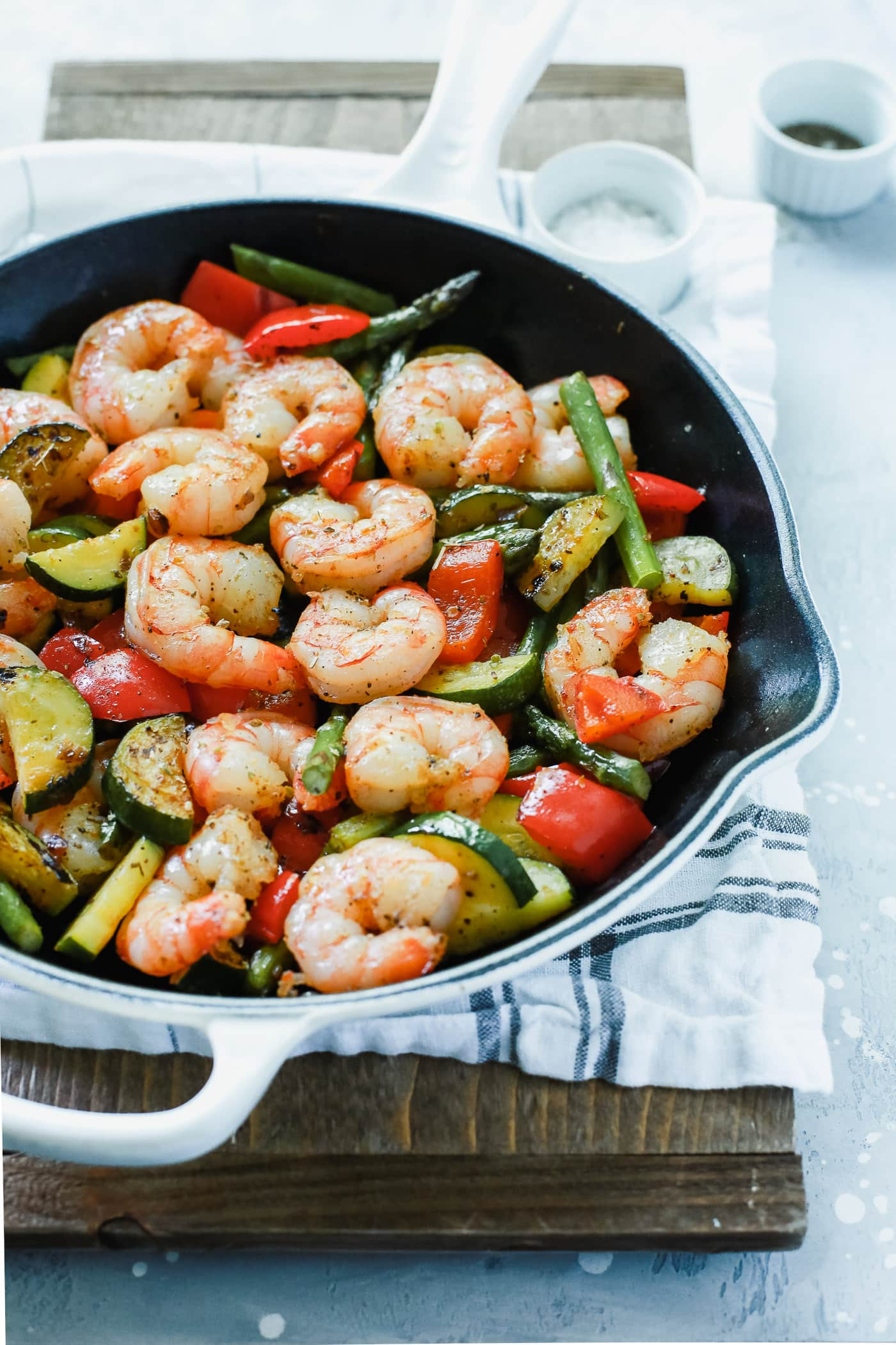 A white cast iron with shrimp and vegetables inside.