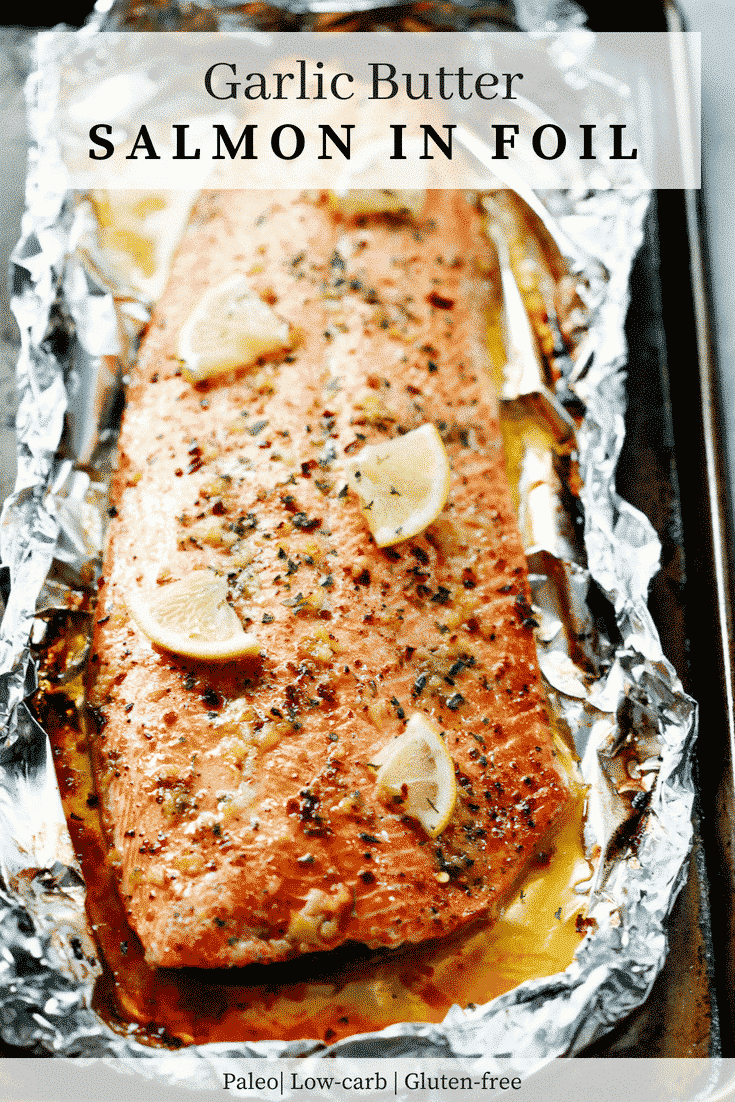overhead view of wild salmon fillet with lemon slices and garlic butter