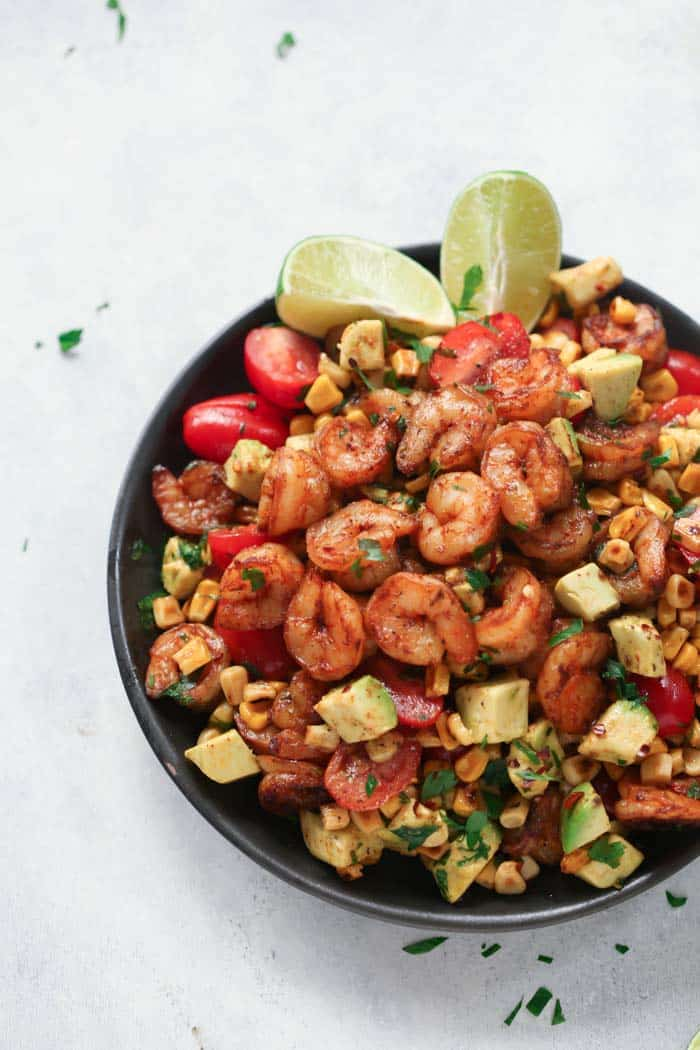 A black bowl containing corn shrimp salad with lime wedges.