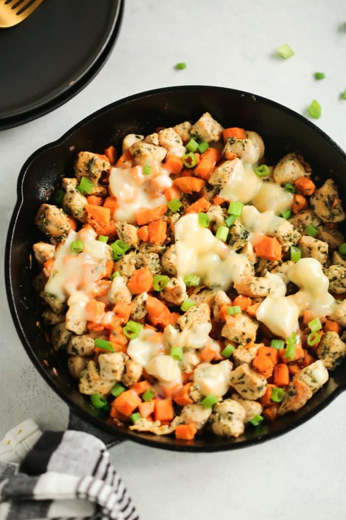 One-Pan Dinner Recipe - Black cast iron with sweet potato pesto chicken.