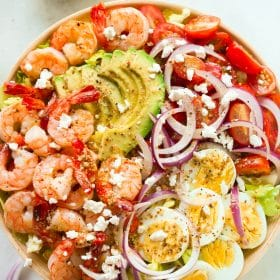 A bowl containing shrimp avocado tomato salad.