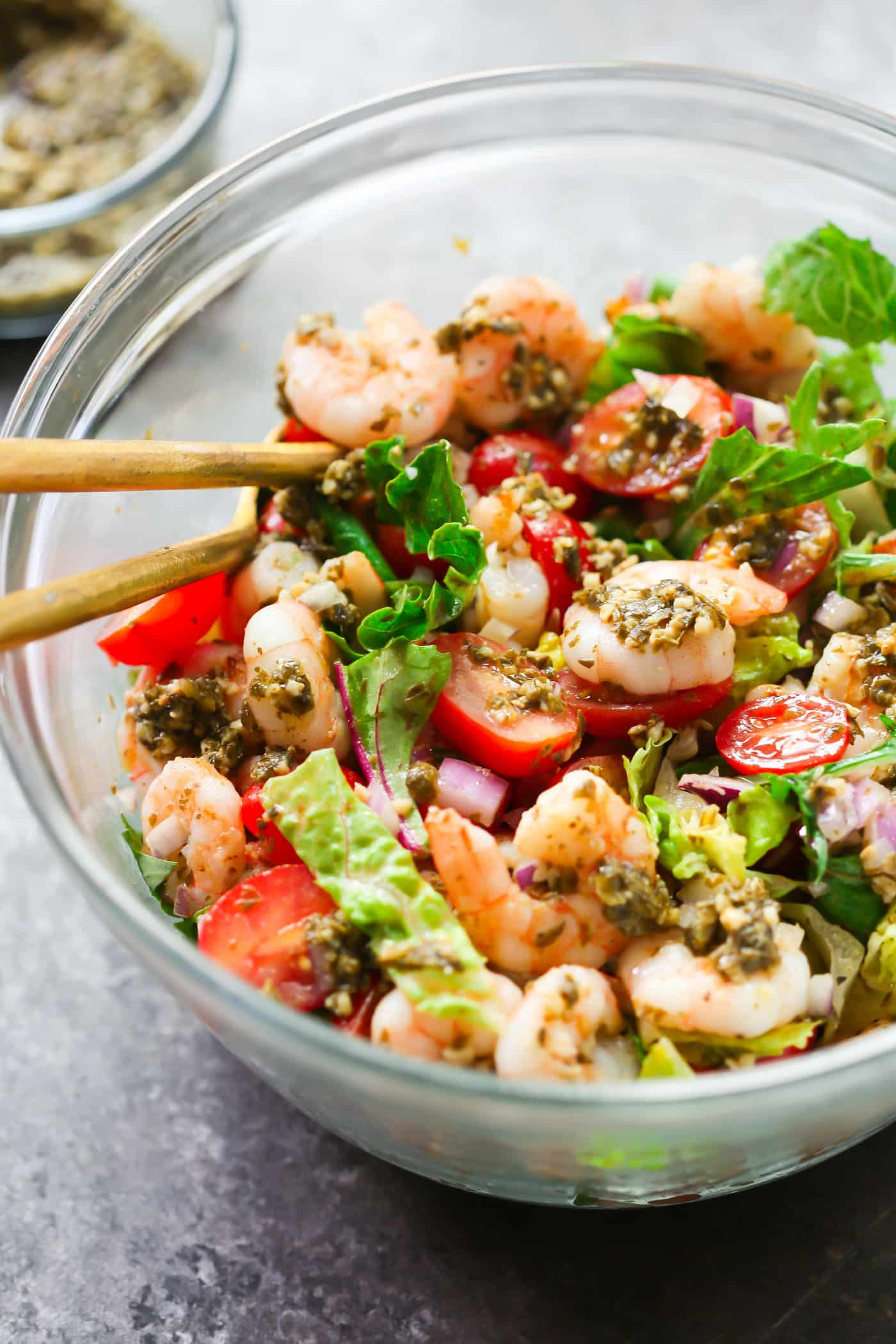 A glass bowl containing pesto shrimp tomato salad.