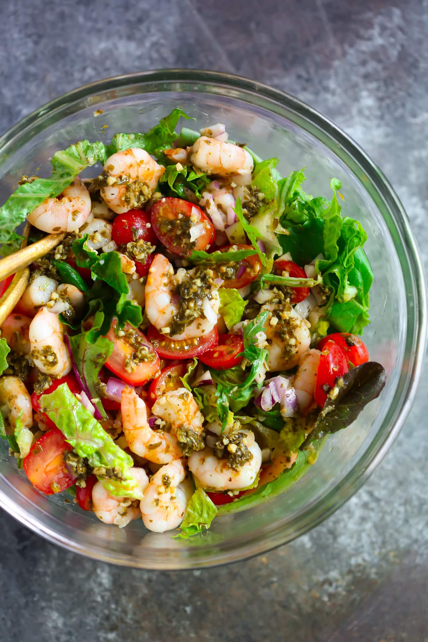 Glass bowl containing pesto shrimp tomato salad.