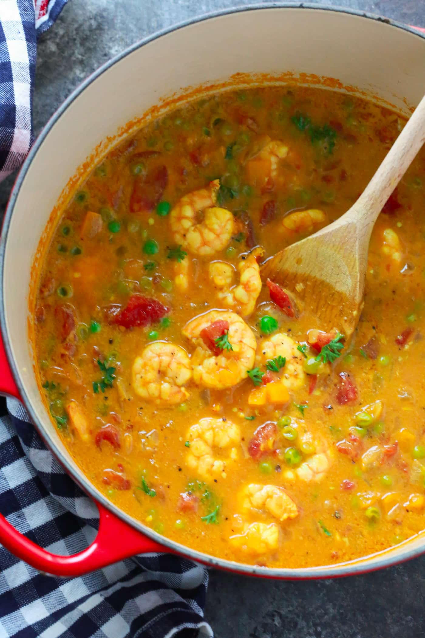 A red dutch oven with a coconut curry shrimp recipe inside.