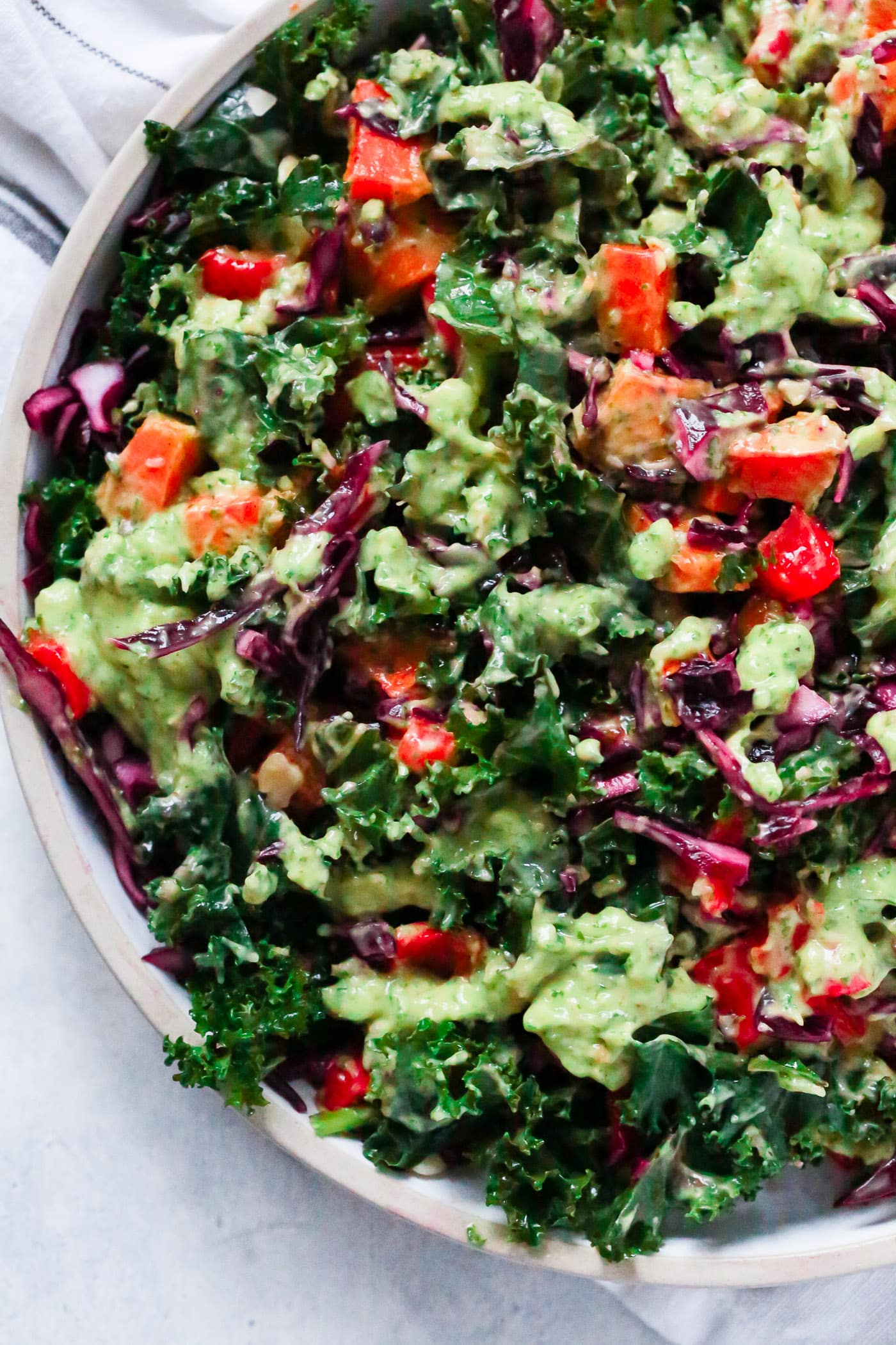 Overhead photo of a large bowl of kale salad with avocado dressing.
