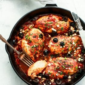 overhead view of a white skillet containing Mediterranean Chicken breast