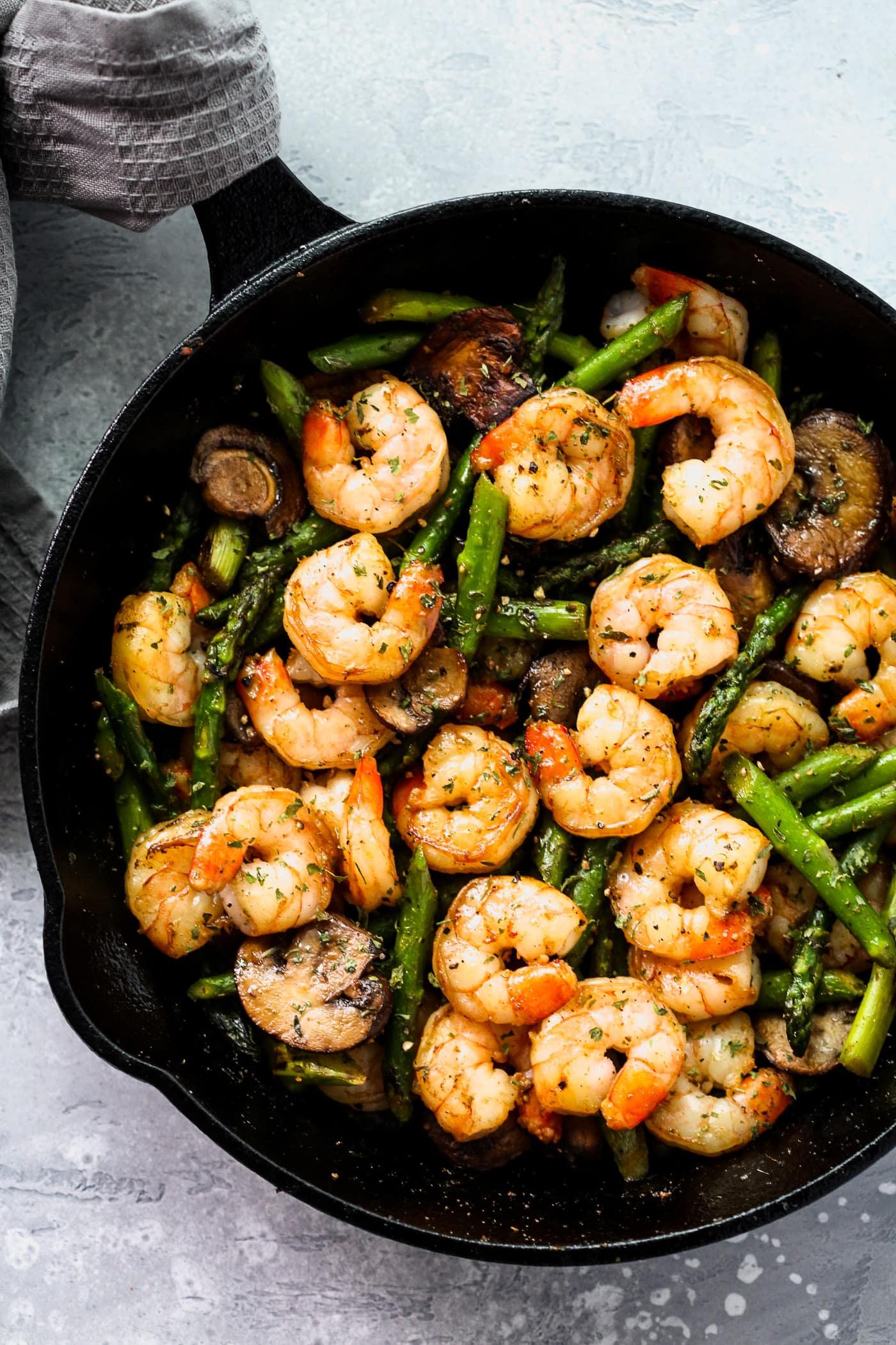 A black cast iron with shrimp and asparagus. - Healthy Shrimp Dinner Recipes