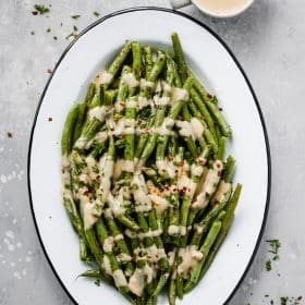 An oval serving platter with roasted green beans with spicy tahini sauce.