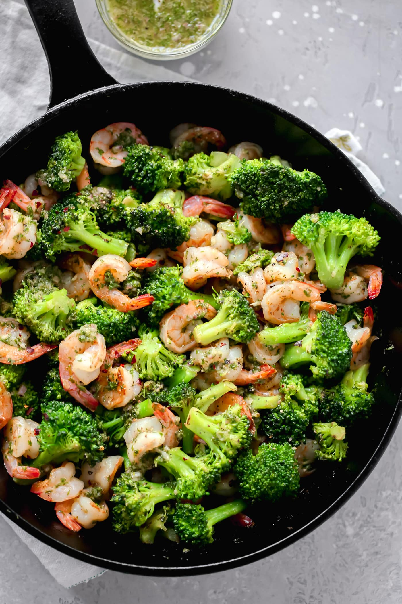 One-Pan Dinner Recipe - A cast iron with chimichurri shrimp and broccoli.