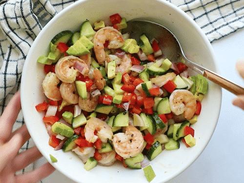 overhead view of shrimp avocado cucumber salad bowl