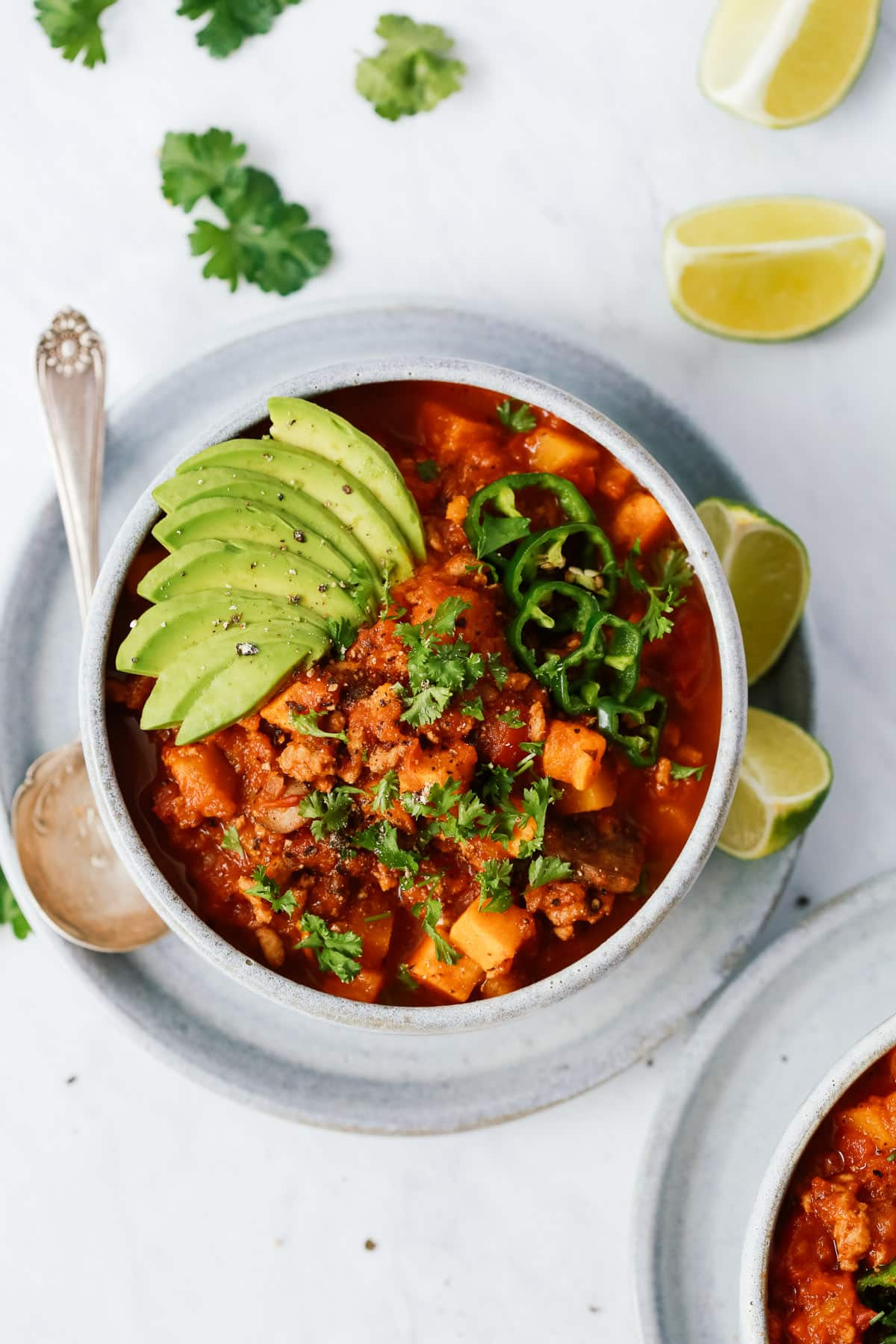 Bowl of sweet potato chili with avocado as garnish and limes around it.