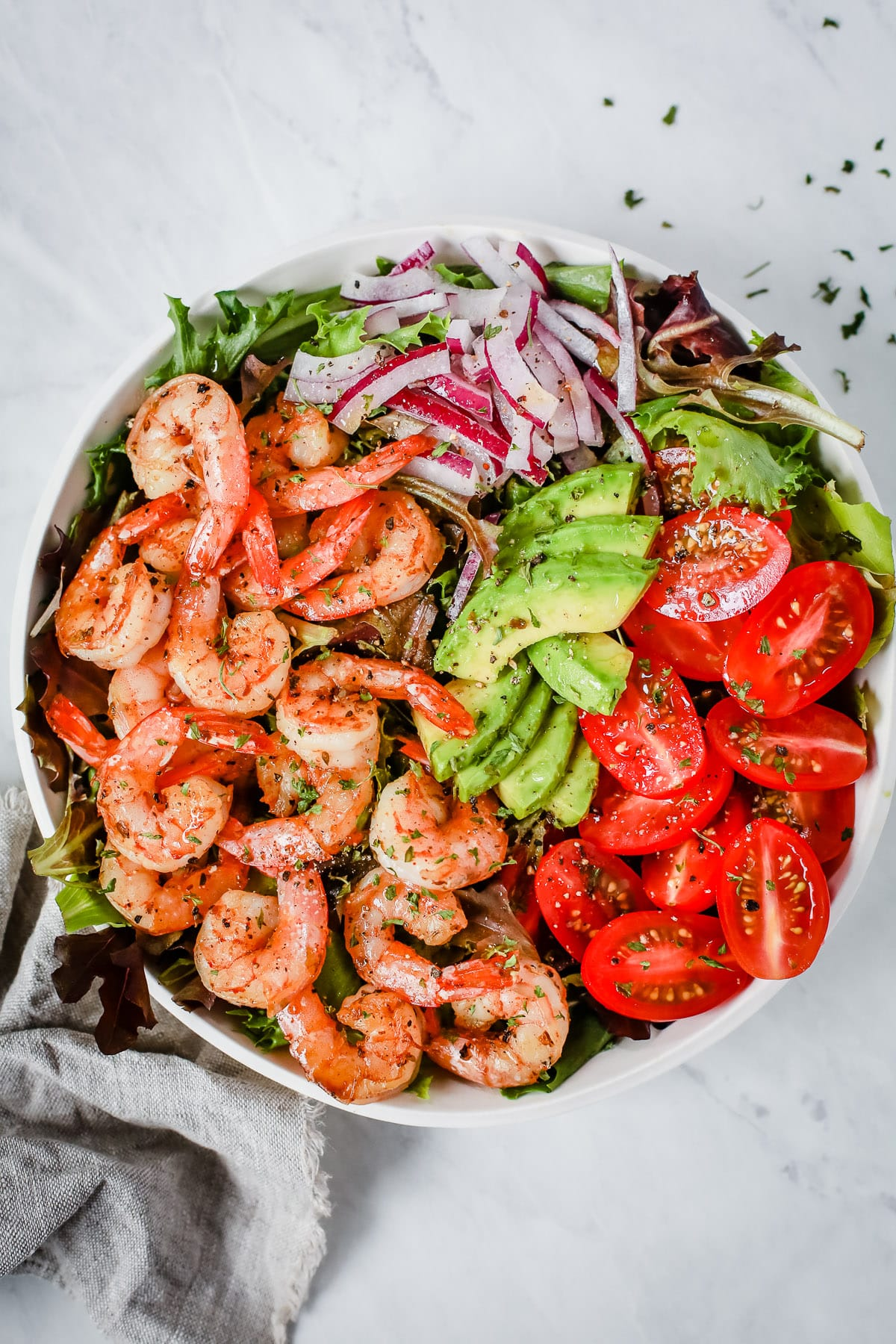 A bowl with shrimp, tomatoes, avocados, onions, and greens.