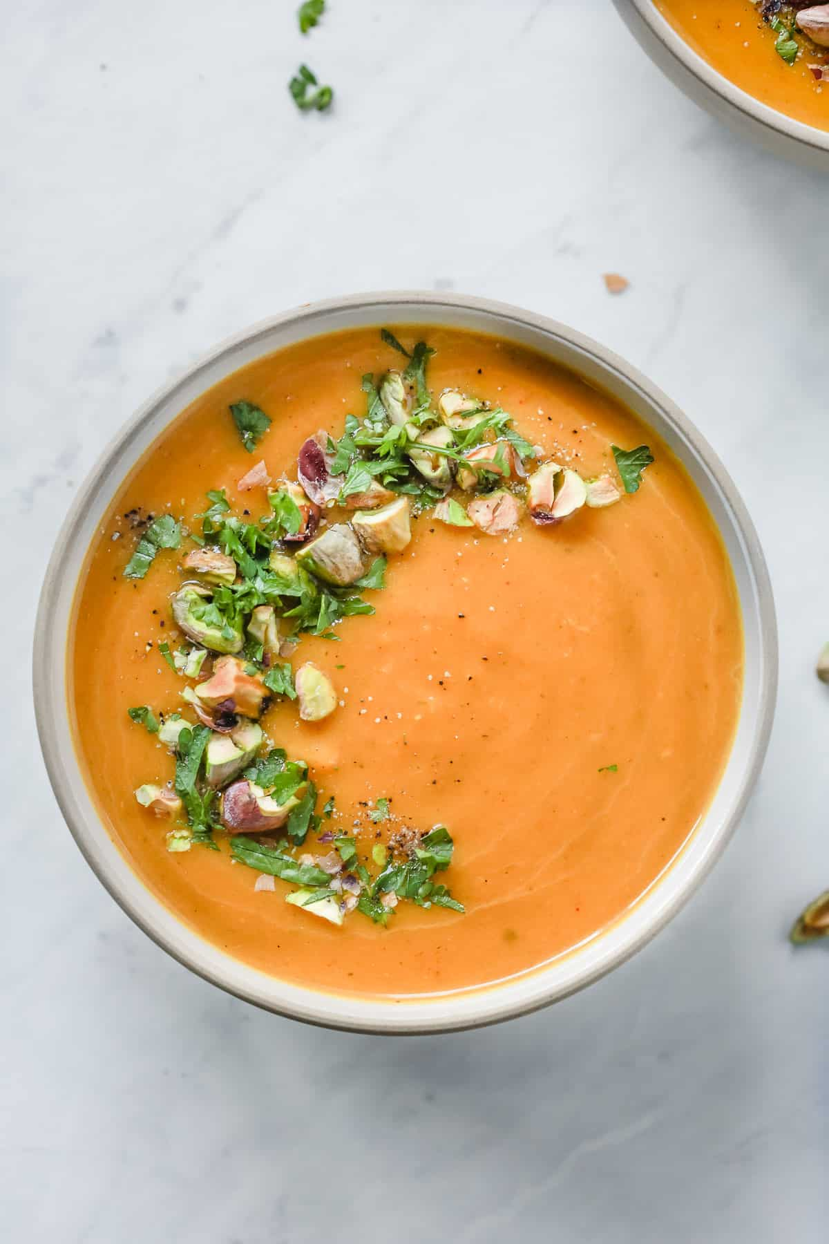Overhead photo of a white bowl with butternut squash soup with garnish.