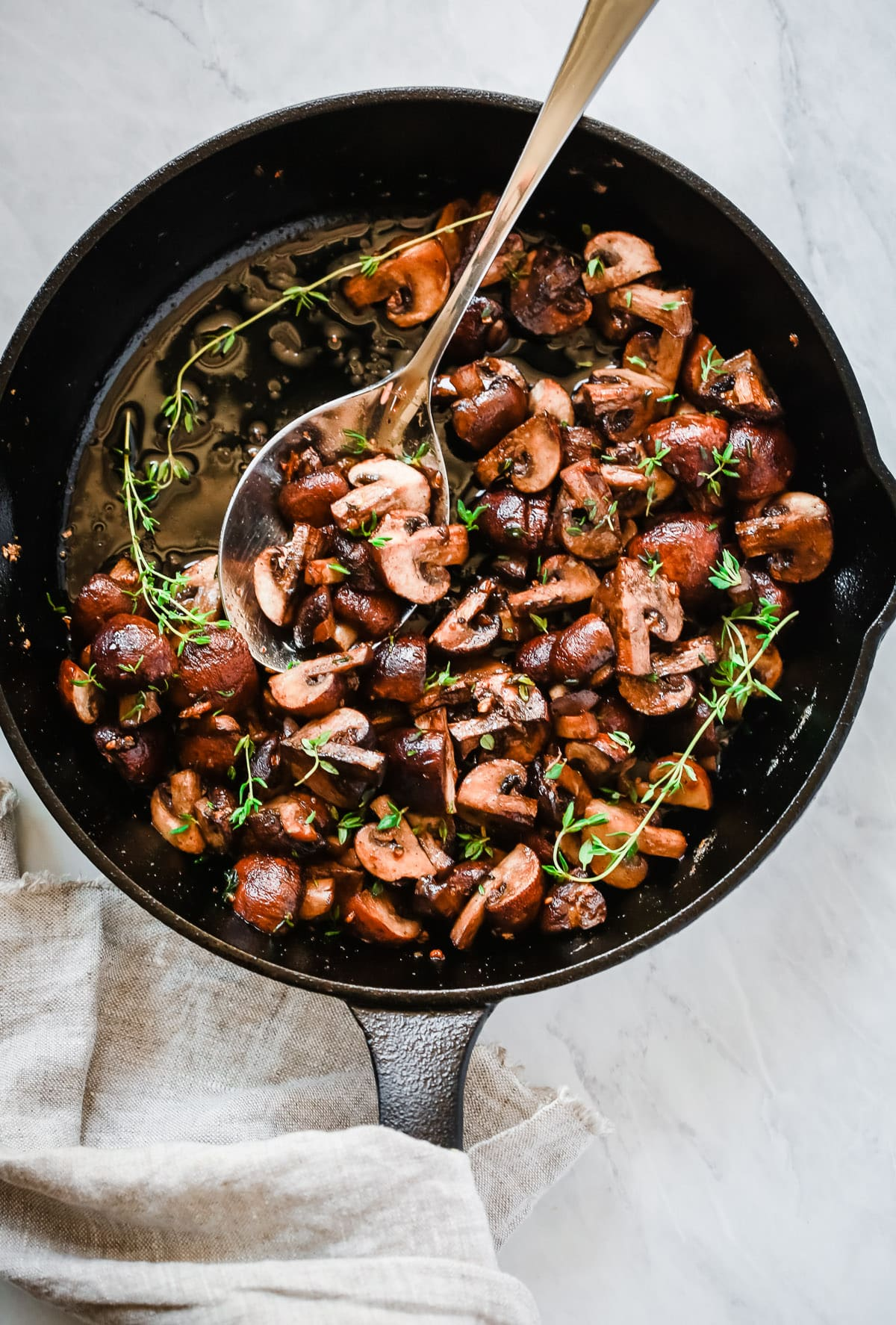 Overhead photo of a cast iron pan with garlic butter mushrooms inside.