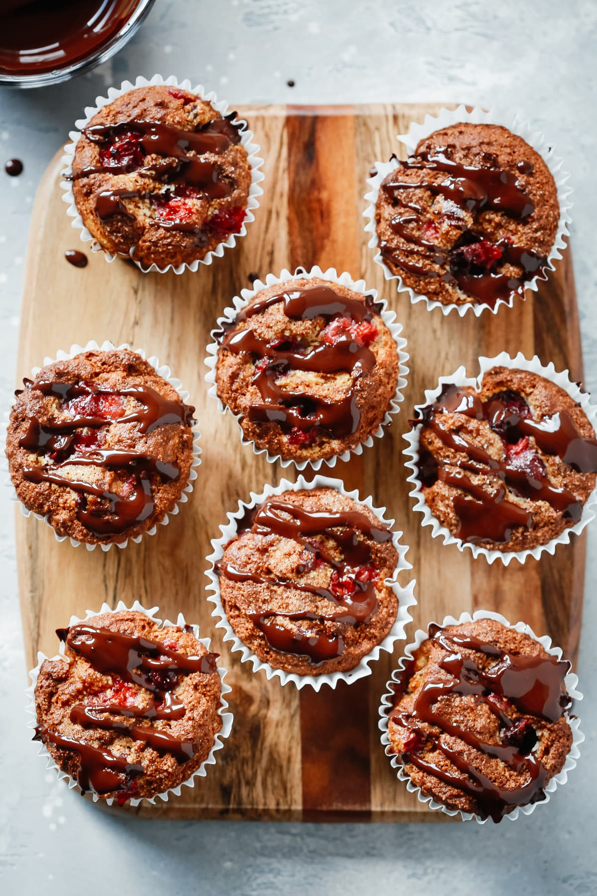 8 Almond Flour Cranberry Muffins on a wood board