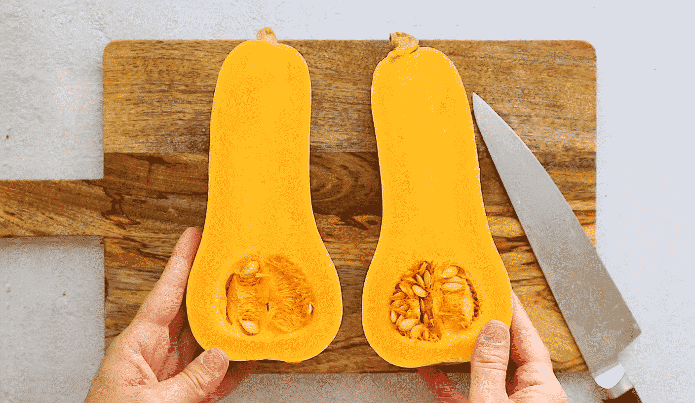 butternut squash cut in half lengthwise on a wooden cutting board