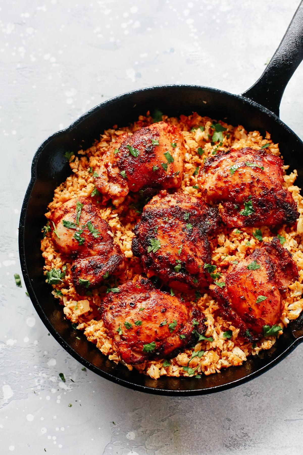 Black skillet with spicy chicken and cauliflower rice.