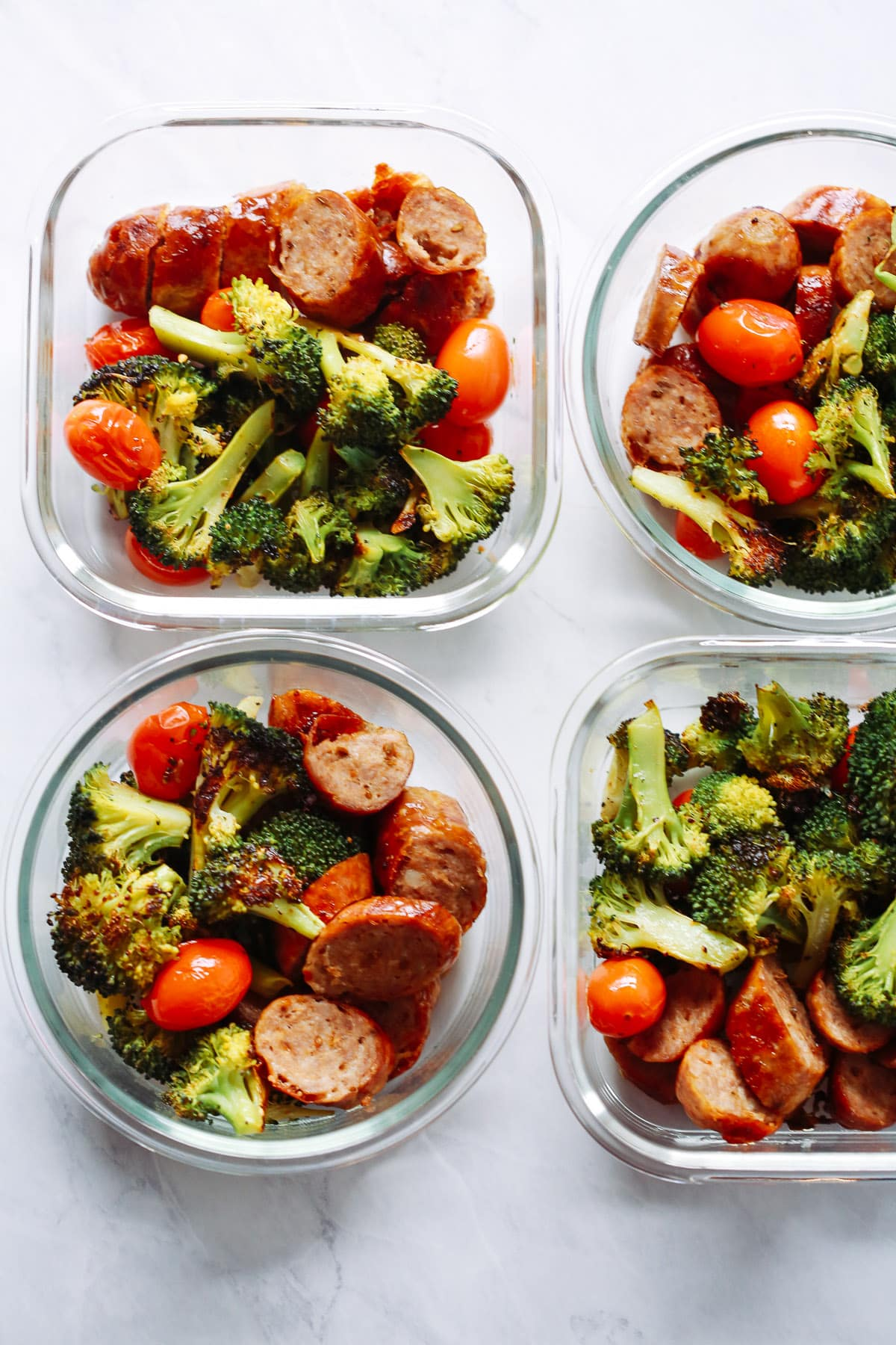Two square and two circular meal prep containers containing sausage and vegetables.