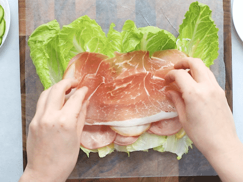 overhead view of lettuce wrap with deli meat on a wooden board