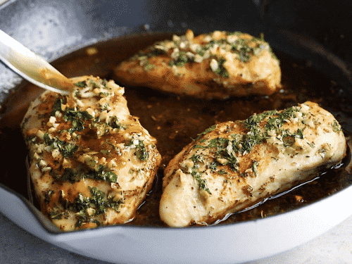 close up view of someone three chicken breast with garlic butter sauce in a cast iron skillet