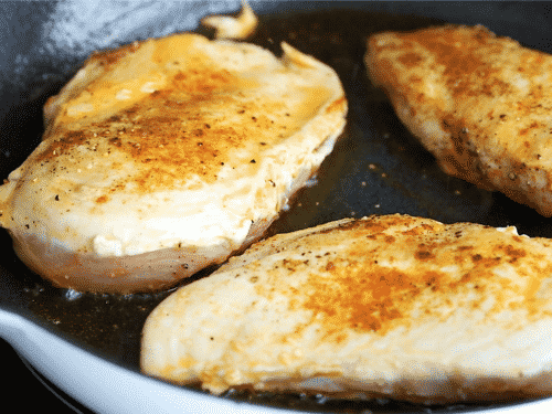 A close up of chicken breast being cooking in a cast iron skillet