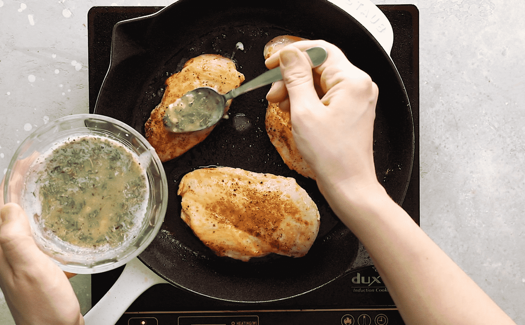 overhead view of someone pouring melted butter over two chicken breast in a cast iron skillet