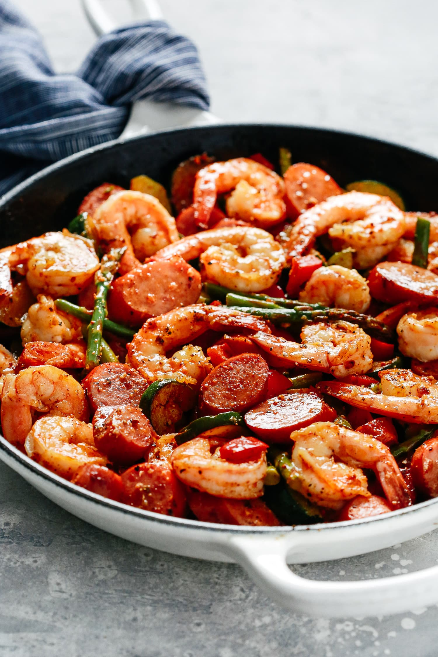 A white skillet with shrimp, sausage, and asparagus.