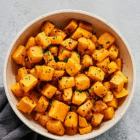 Overhead photo of a white bowl of roasted butternut squash.