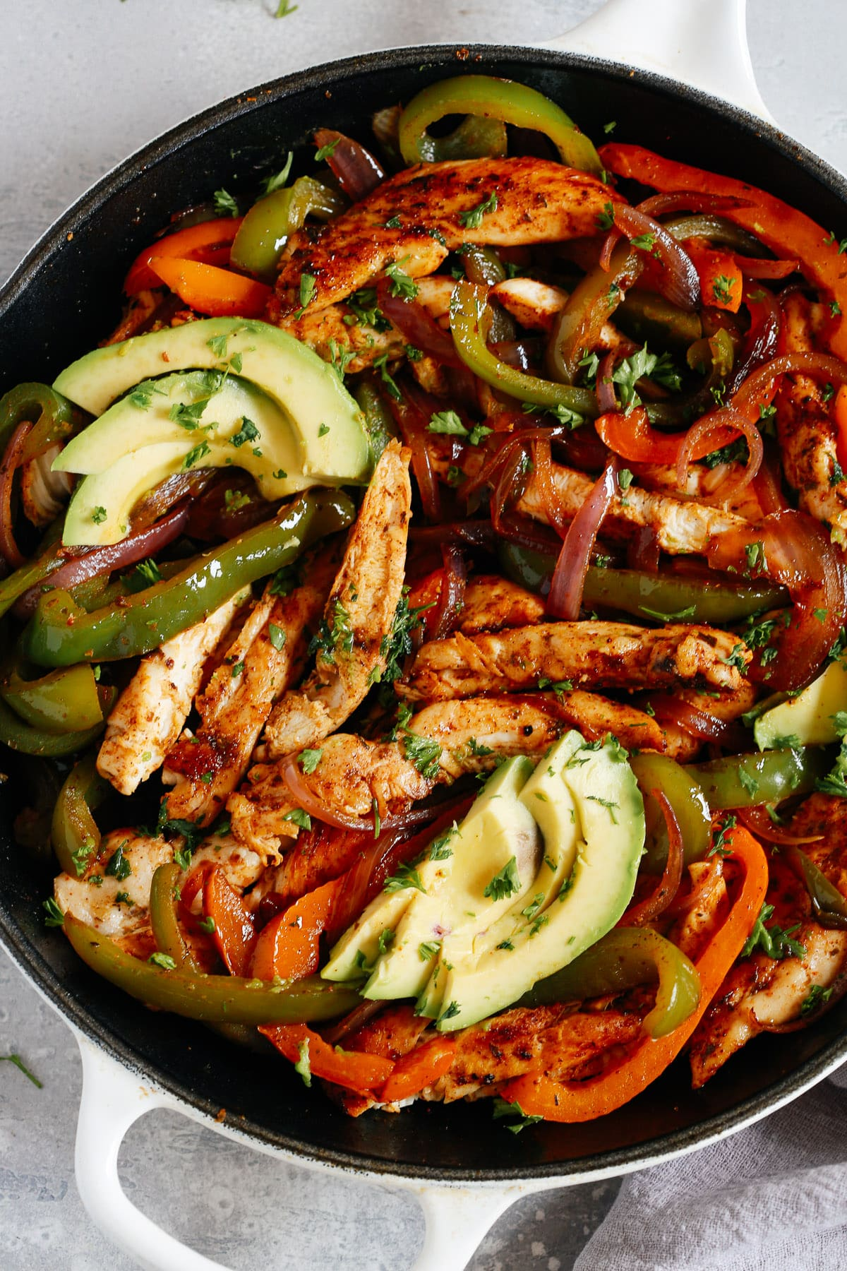 A white skillet with chicken fajitas, bell peppers, and avocado slices.
